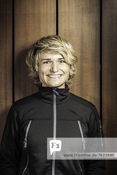 Lächelnde Frau an der Holzwand