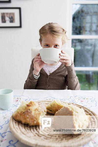 Mädchen trinkt Suppe aus der Schüssel bei Tisch