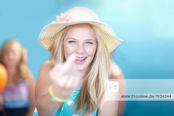 Teenage girl making rude hand gesture