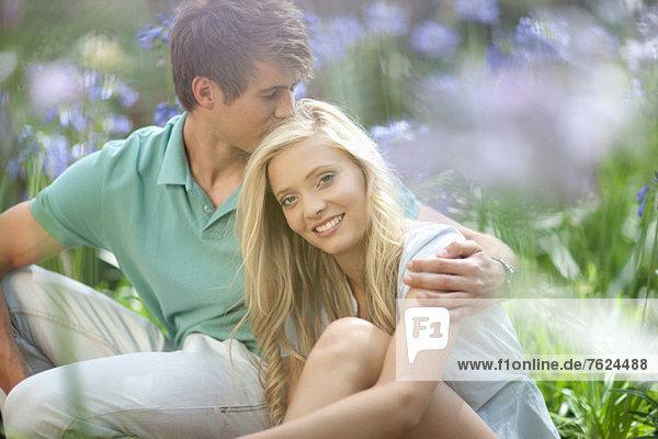 Lächelndes Paar in hohen Pflanzen sitzend
