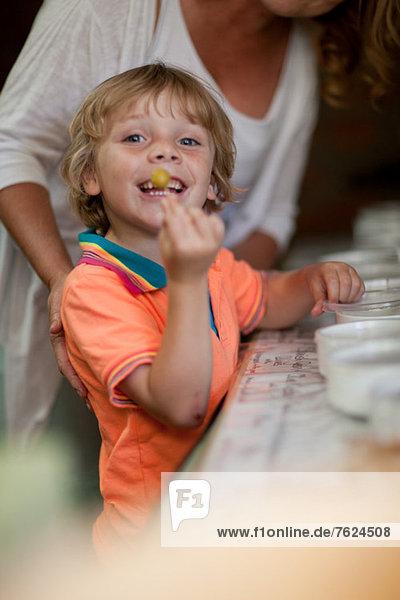 Lächelnder Junge mit Oliven im Lebensmittelgeschäft