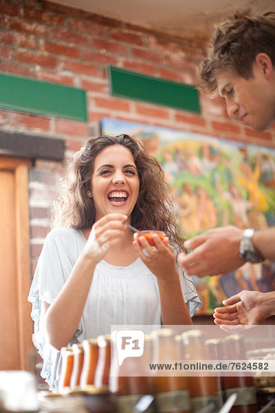 Couple tasting preserves in grocery