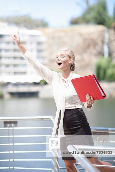Geschäftsfrau winkt vom Balkon aus