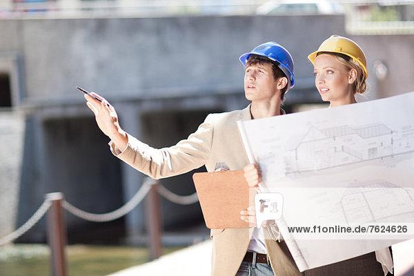 Geschäftsleute beim Lesen von Bauplänen
