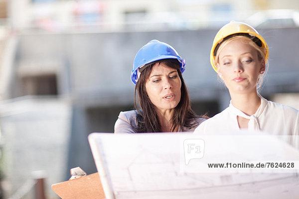 Geschäftsfrauen beim Lesen von Bauplänen