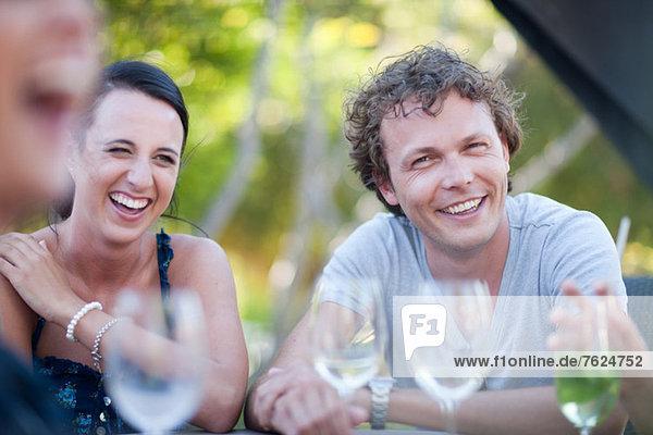 Freunde bei einem Drink am Tisch im Freien