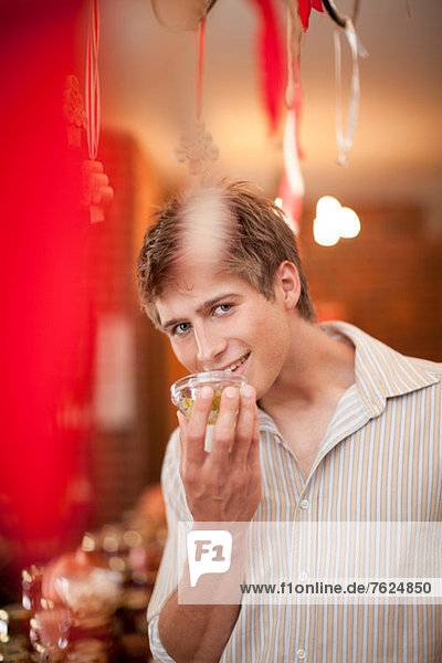 Man smelling preserves in grocery