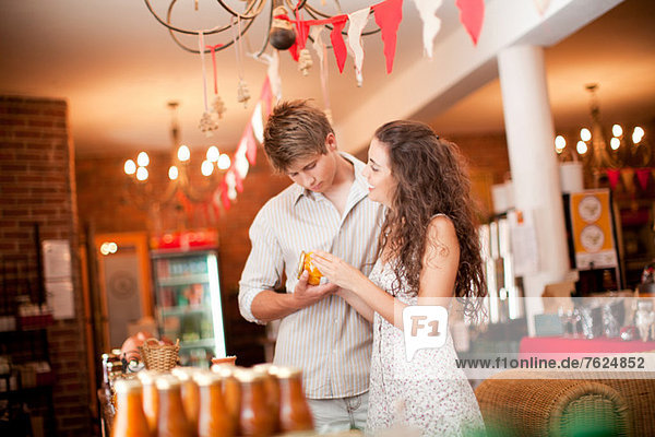 Couple examining preserves in grocery