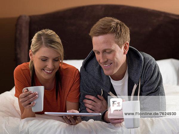 Paar mit Tablet-Computer auf dem Bett