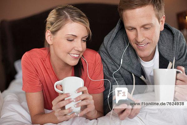 Paar hört Kopfhörer auf dem Bett