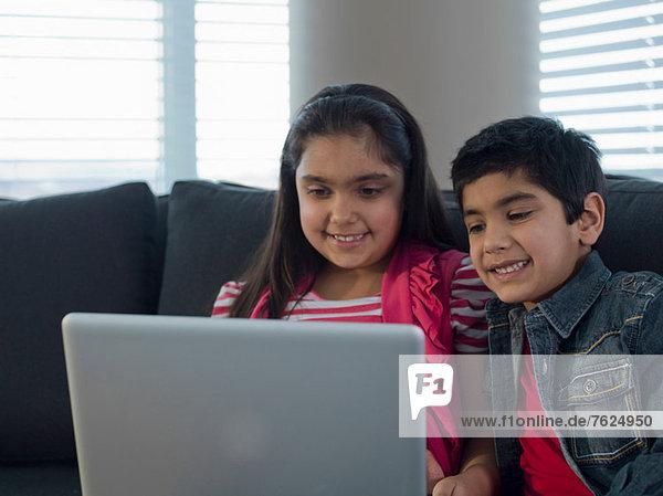 Children using laptop together on sofa