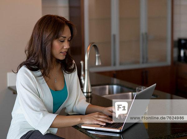 Frau mit Laptop an der Theke