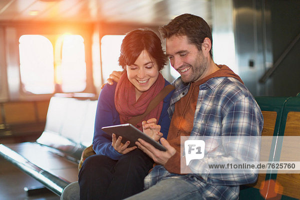 Paar mit Tablet-Computer auf der Fähre