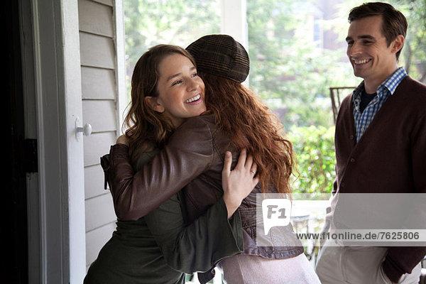 Women hugging at front door