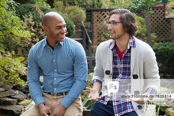 Smiling men talking in backyard