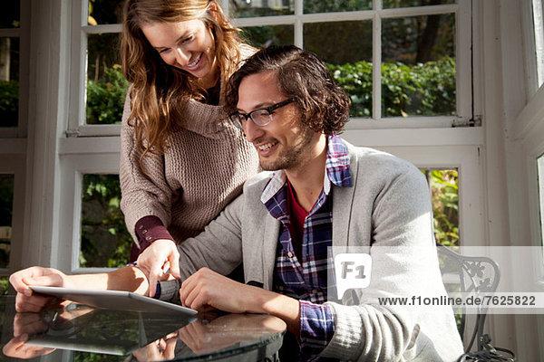 Paar mit Tablet-Computer am Tisch