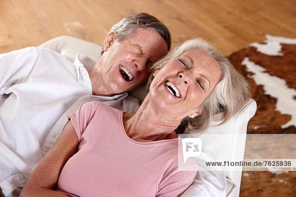 Älteres Paar lacht auf dem Sofa