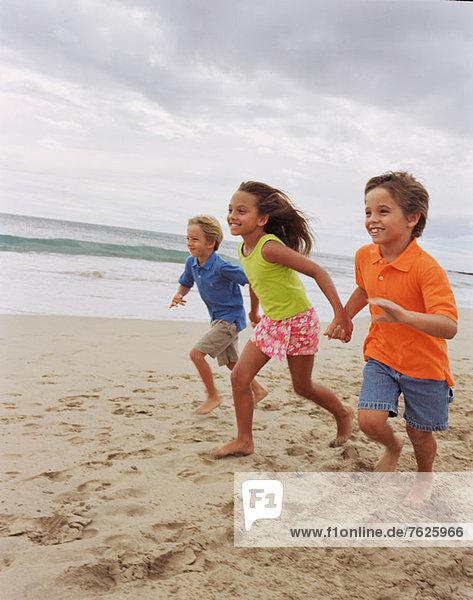 Kinder beim gemeinsamen Laufen am Strand