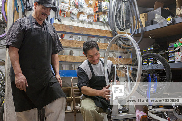 Mechanics working in bicycle shop