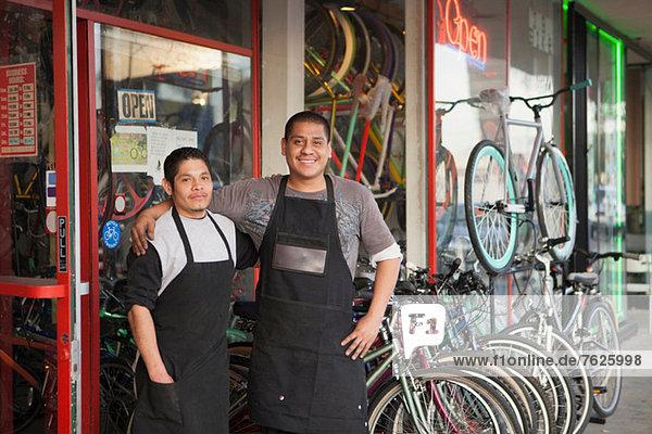 Mechaniker lächeln vor dem Fahrradgeschäft