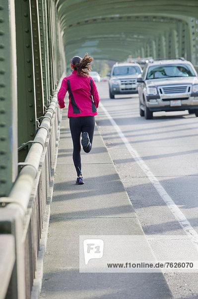 Frau läuft auf Stadtbrücke