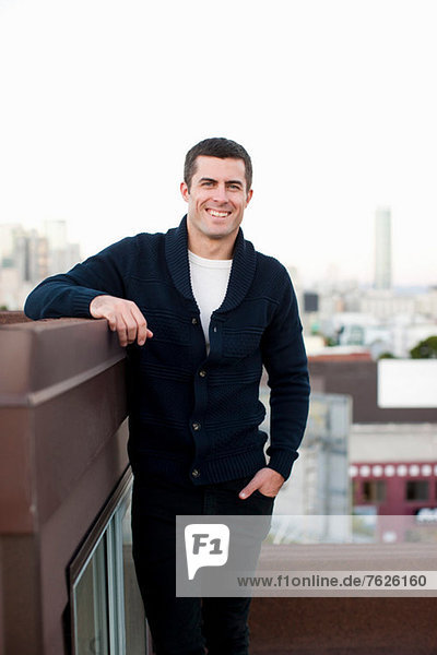 Smiling man standing on urban balcony