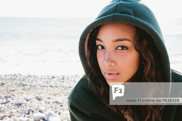 Woman wearing hoodie on beach