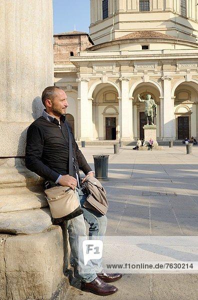 Tourist Mann ruht an einer Säule der Arkade vor der alten Kirche im Stadtzentrum  im Hintergrund der Platz und der monumentale Eingang
