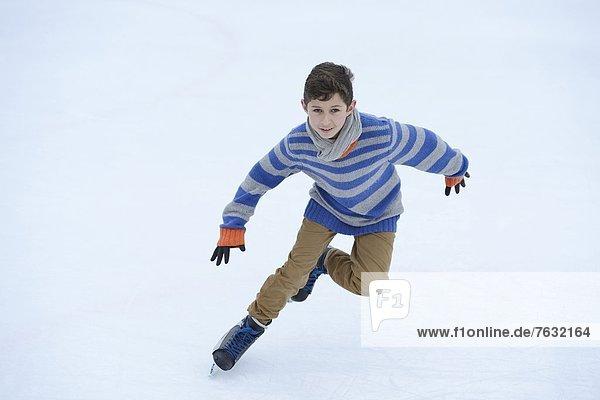 Junge läuft Schlittschuh auf einem gefrorenen See Junge läuft Schlittschuh auf einem gefrorenen See