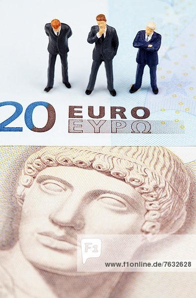 Miniatur-Figuren von Geschäftsleuten auf Euro- und Drachmen-Banknoten