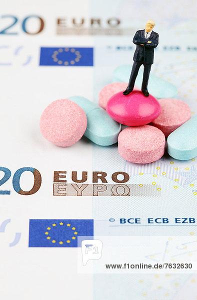 Miniatur-Figur eines Geschäftsmannes im Stand auf Pillen und einer Euro-Banknote