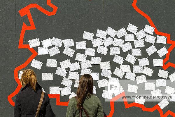 Zwei jugendliche Touristinnen stehen vor einer Mauer mit Postkarten die anläßlich der 775-Jahr Feier-Berlins am alten Schlossplatz in Berlin Mitte aufgestellt war  Berlin  Deutschland  Europa Zwei jugendliche Touristinnen stehen vor einer Mauer mit Postkarten die anläßlich der 775-Jahr Feier-Berlins am alten Schlossplatz in Berlin Mitte aufgestellt war, Berlin, Deutschland, Europa