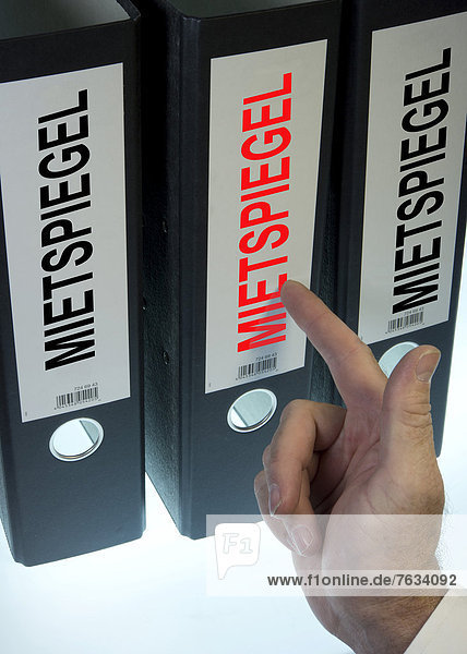 'Hand pointing to a file folder labeled ''Mietspiegel''  German for ''rent index'''