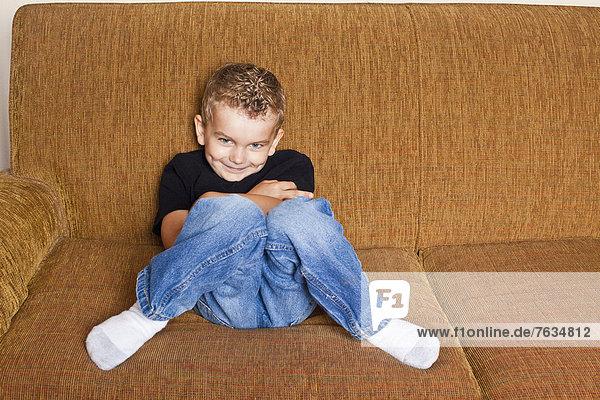 Caucasian boy sitting on sofa
