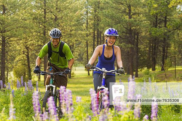 Couple riding mountain bikes in meadow