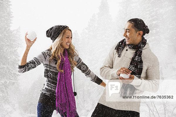 Paar mit Schneeball kämpfen im freien