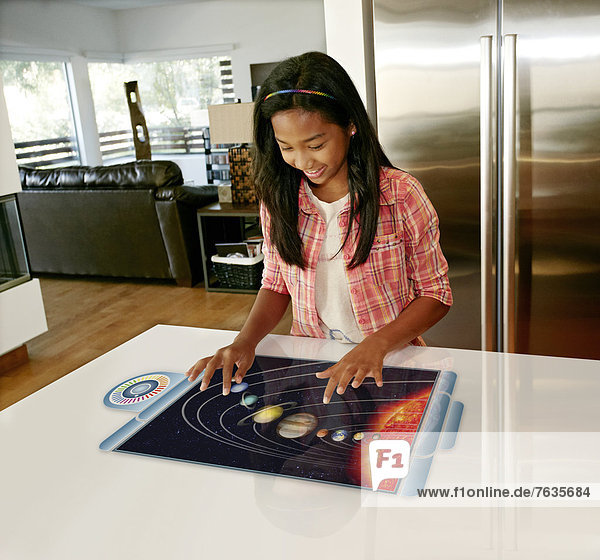 Mixed race girl playing on computer in table