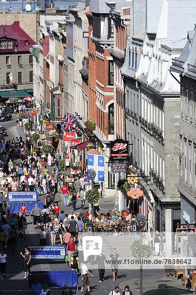 Hochformat  Farbaufnahme  Farbe  Frau  Mann  Mensch  Menschen  gehen  über  Straße  Erhöhte Ansicht  Aufsicht  beschäftigt  kaufen  Kunde  Laden  Jeans  Fußgänger  Altstadt  Fernsehantenne  Kanada  Quebec  Quebec City