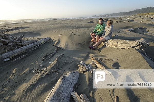 Vereinigte Staaten von Amerika USA sitzend Frau Mann Mensch Menschen Küste Natur ungestüm Außenaufnahme Bier Treibholz