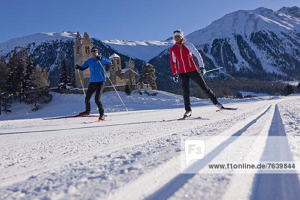 Frau Winter Mann Kirche Ski Langlaufski Kanton Graubünden Wintersport