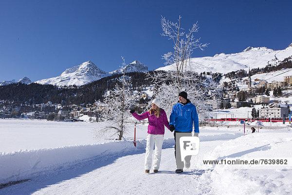 Frau Winter Mann gehen Weg See wandern Kanton Graubünden Wanderweg trekking Wintersport