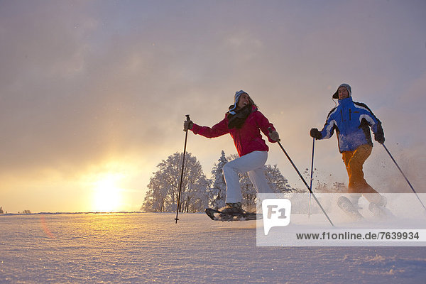 Schneeschuh Frau Winter Mann gehen Sonnenuntergang wandern Schnee Wintersport