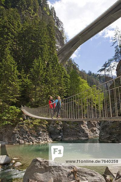Hängebrücke Frau Mann gehen Weg Brücke wandern Schlucht Kanton Graubünden Wanderweg trekking