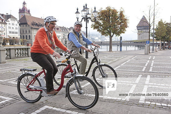 Seniors  couple  electric bicycle  Flyer  eBike town  city  bicycle  bicycles  bike  riding a bicycle  town  city  Switzerland  Europe  bicycle  bike  Lucerne  Luzern