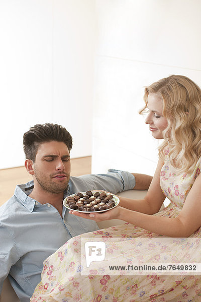 Woman serving chocolates to a man
