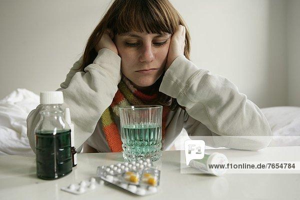 Kranke Frau sitzt vor Medikamenten