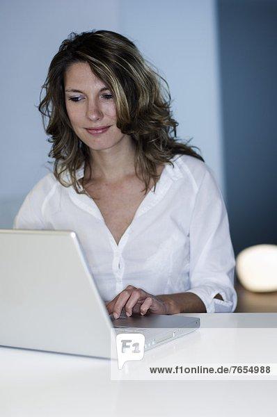 Frau arbeitet konzentriert an einem Laptop