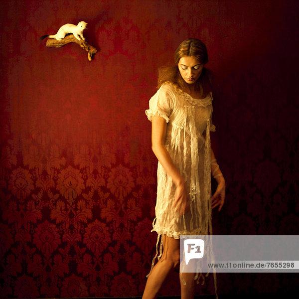Junge Frau in weißem Nachthemd vor roter Tapete