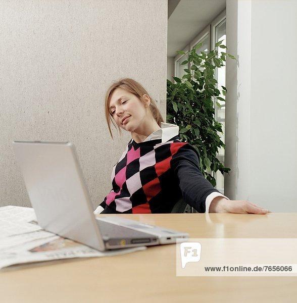 Junge Frau sitzt im Büro am Schreibtisch