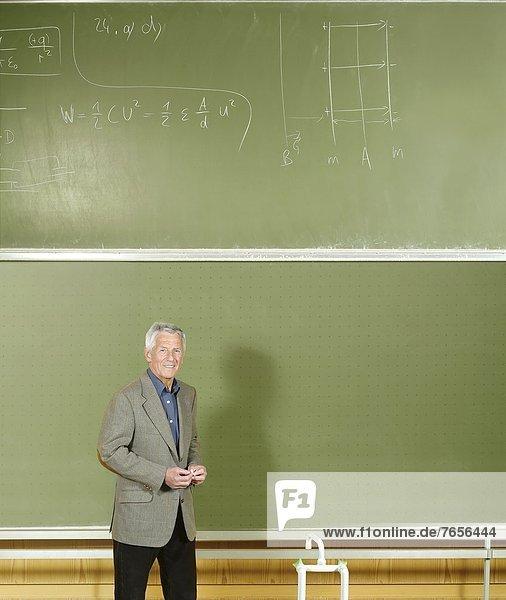 Grauhaariger Mann an einem Pult vor einer Tafel mit physikalischen Gleichungen - Physiklehrer - Studium